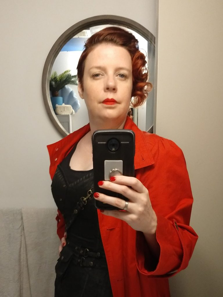 A selfie in front of the mirror by Victoria, who has curled her hair and is wearing a black corset and red coat.