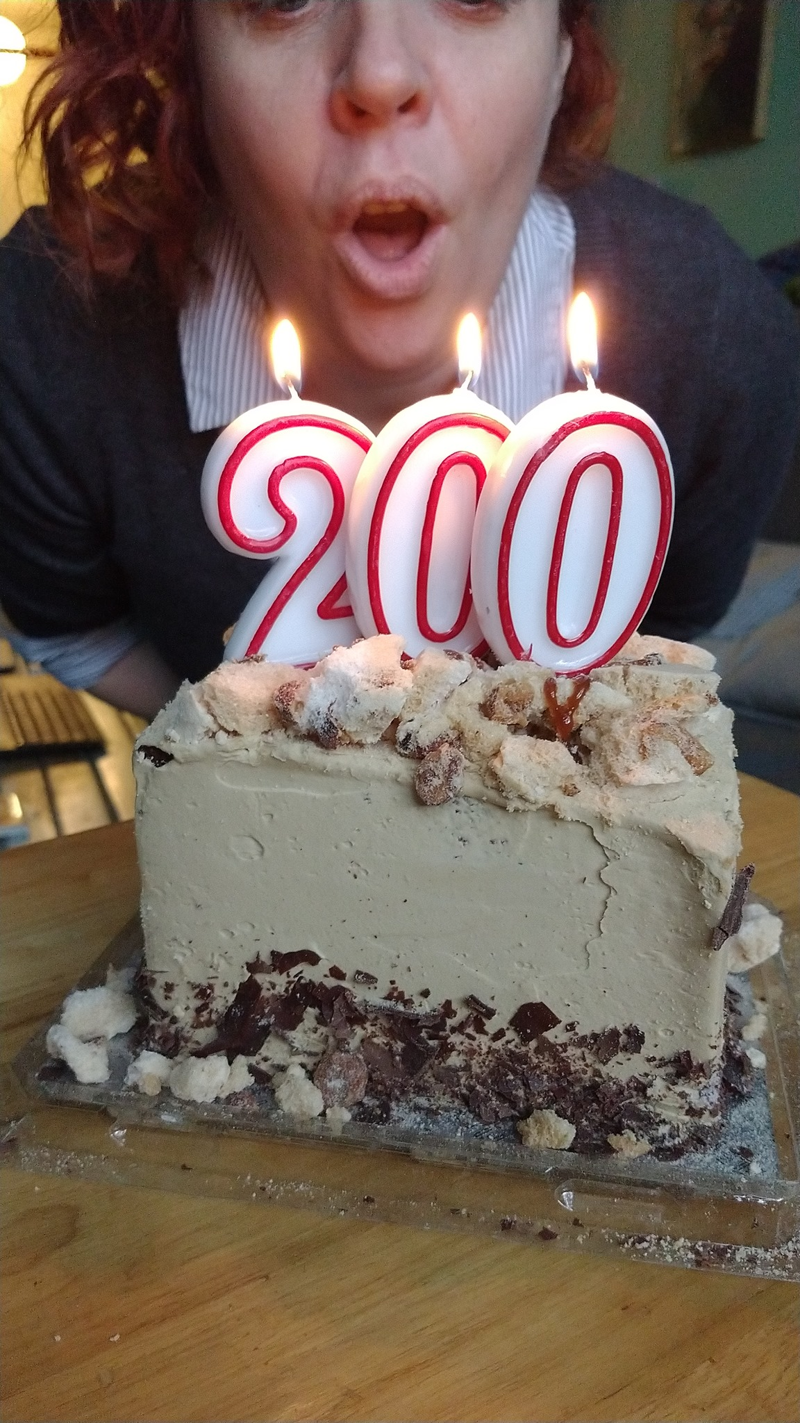 Blowing out candles in the shape of the number 200.